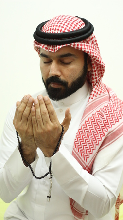 A Handsome Arab Muslim Model Praying With Closed Eyes In The Month Of Ramadan