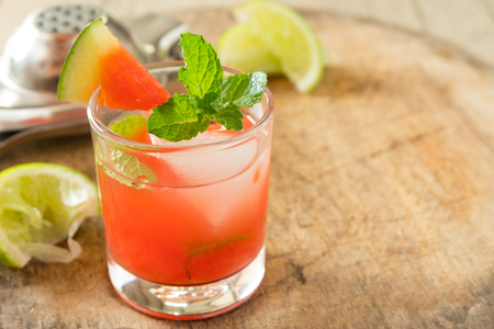watermelon and vodka mix with  peppermint on top in small glass with one of watermelon pice and squeeze the lemon set on chopping bord