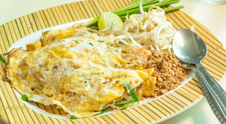 Thai noodle is called Pad Thai in yellow plate with nut lemon and bean sprouts.