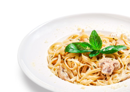 freshly prepared noodles with cheese and mushroom sauce in bowl on white background