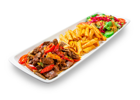 pasta with meat, peppers and vegetables drizzled with sauce in plate on white background