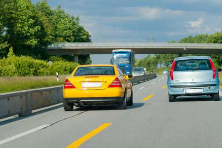 temporary: yellow car outstrips gray car on highway with temporary marking Stock Photo