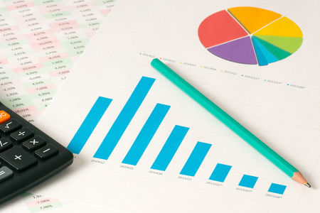 pensil: multi color pie and bar charts with calculator and pensil with fall trend Stock Photo