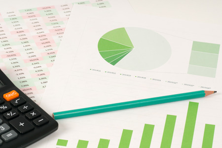 bar charts: circulares y de barras verdes con la calculadora Foto de archivo