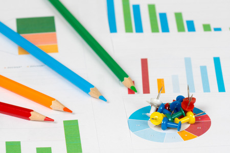 grafica de barras: colorful pie and bar charts with four pencils and pins