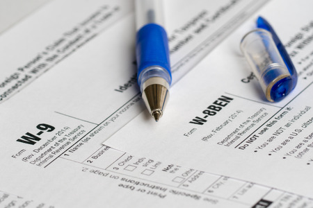 withholding: tax reporting two forms with opened blue pen Stock Photo