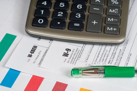 reporting: tax reporting forms with closed green pen and calculator Stock Photo