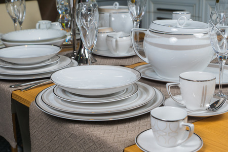 dinnerware: white luxury ceramic dinnerware set on wooden table Stock Photo