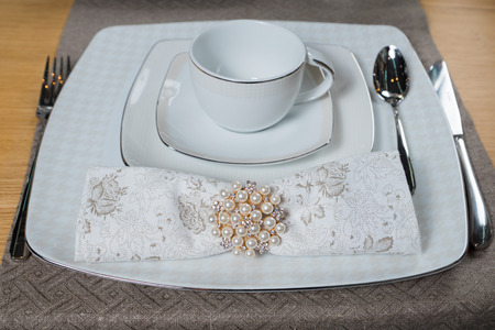 dinnerware: white classical luxury dinnerware set on wooden table