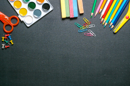 back to school supplies: paints, scissors, pencils and chulks on black chalkboard Stock Photo