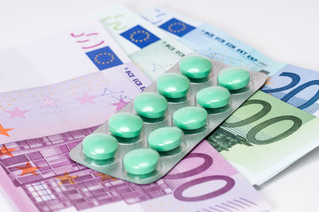 analgesic: green analgesic pills in blister with euro banknotes