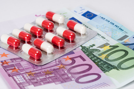 the antibiotic: white and red antibiotic capsules in blister with euro banknotes