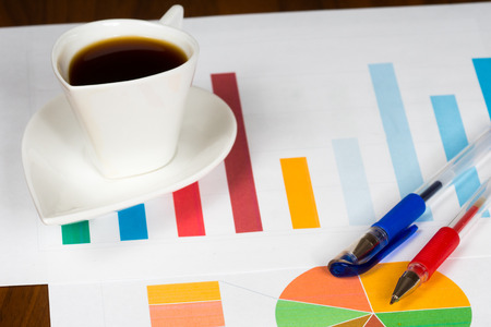 graficas de pastel: taza de café con las cartas y plumas multicolor de la barra y de la empanada