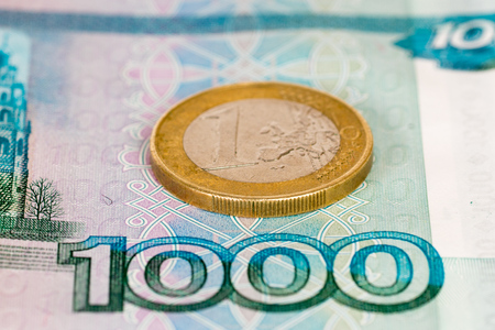 one hundred euro banknote: one thousand roubles banknote with one euro coin