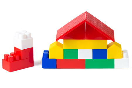 building structure: colorful plastic building blocks house on white background