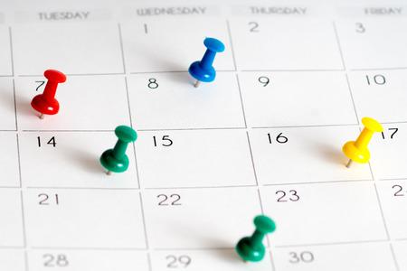 thumb tack: colorful pins on calendar grid Stock Photo