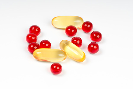 semitransparent: vitamin e and cod liver oil capsules on white