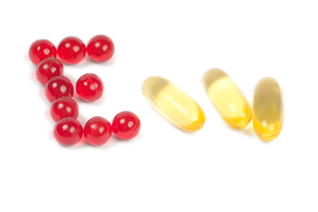 vitamin e letter and cod liver oil capsules on white
