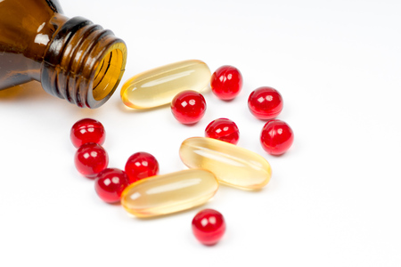 vitamin e and fish oil capsules with opened bottle on white