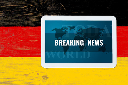 breaking news splash screen on tablet pc over painted germany flag