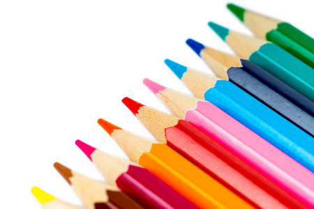 Close-up of colorful pencils in line on white background