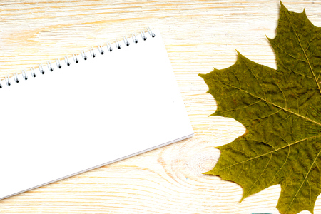 notepad with green maple leaf on white wooden planks, autumn card template