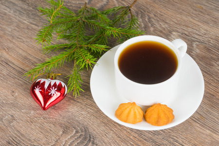coffee cup with cookies and fir tree branch on rustic wooden background