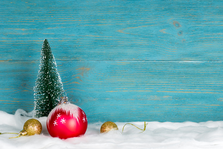 evergreen fir tree and xmas decorations, snowy christmas composition, turquoise wooden background, copy space
