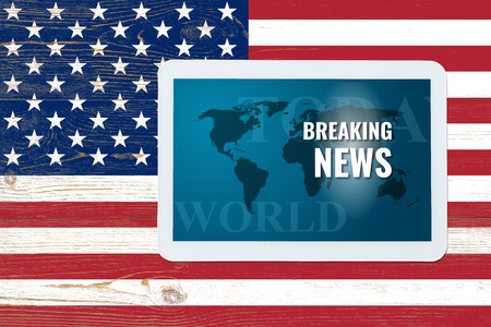 breaking news splash screen on tablet pc over painted united states flag