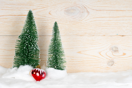 two evergreen fir trees and red heart, snowy christmas composition, wooden background, copy space