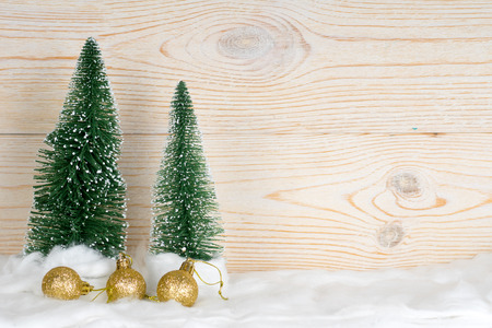 two evergreen fir trees and golden xmas baubles, snowy christmas composition, wooden background, copy space Zdjęcie Seryjne