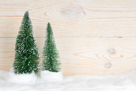 two evergreen fir trees, snowy christmas composition, wooden background, copy space