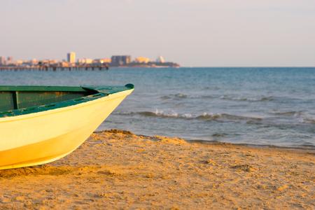fisherman boat on sand near sea