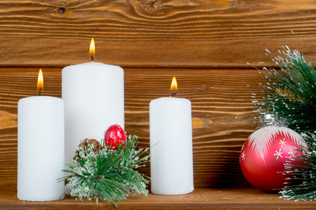 christmas decorations with candles pine brunch and bauble Stock Photo