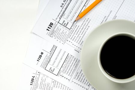 1120 tax forms top view with coffee cup and pencil