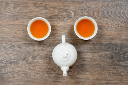 two small bowl with tea and teapot on gray wooden table, good morning concept