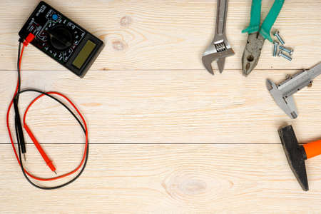 hand tools and multimeter on wooden planks