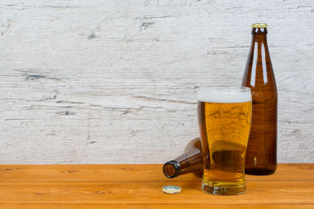 closed and opened beer bottles with full glass on pub table, drunkenness problem concept