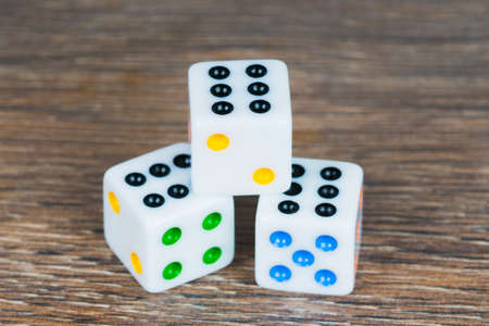 white dices with colorful dots on wooden table