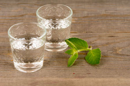 vodka with mint in shot glasses on rustic wooden table Standard-Bild