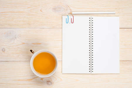 empty notebook with tea cup on white wooden table