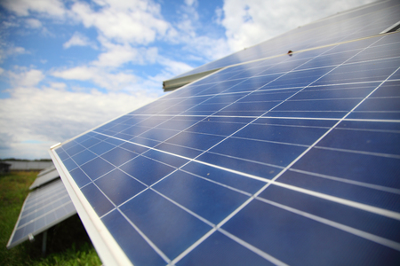 Sunlight gleams off solar panels in field. Solar panels used to generate electricity from sunlight against clouds and sky. Stock Photo