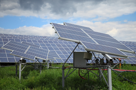 Solar panels used to generate electricity from sunlight against clouds and sky.