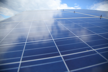 generate: Solar panels used to generate electricity from sunlight against clouds and sky Stock Photo