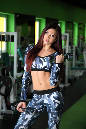 corrects: Slender young girl corrects figure in the gym. Training in the gym for the figure correction.