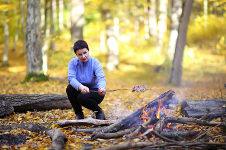 Camping in the forest. Beautiful mature woman on a picnic in the forest. A woman is cooking bacon on a fire, strung on a stick. Stock Photo