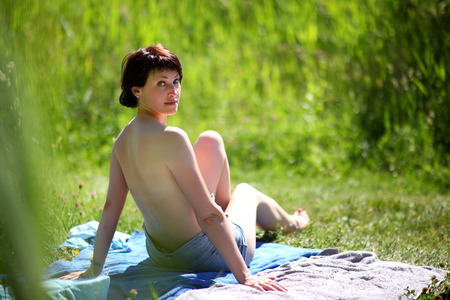 Beach season. Woman on the beach by the lake. Beautiful young woman bathes in the rays of the summer sun on the hill above the river. Archivio Fotografico