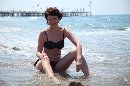 A beautiful woman is basking in the sun in the sea. Young woman sitting on the beach. Beautiful adult woman sunbathing on the beach. Imagens