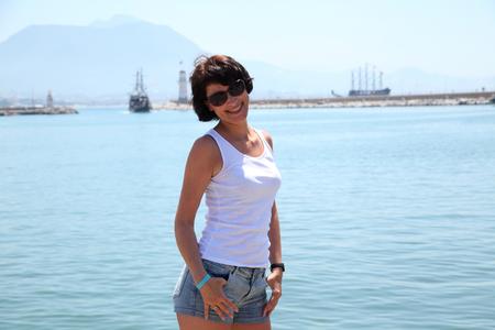 Beautiful adult woman sunbathing on the beach. Imagens
