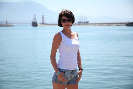 Beautiful adult woman sunbathing on the beach.